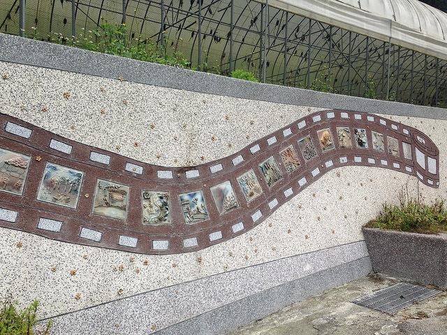 西寶聚落的故事牆,以膠捲形式,鑲嵌著每個時期不同的故事。攝影:廖靜蕙